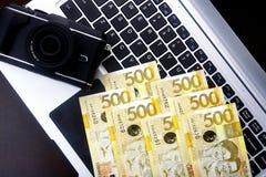 Rechnungen der Kamera und des philippinischen Pesos auf einer Laptop-Computer Lizenzfreie Stockfotografie