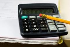 Rechnungen, Dokumente und Papiere mit Taschenrechner Büro des accou Stockbilder