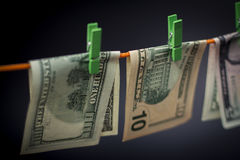 Rechnungen, Dollar sind auf dem Seil mit grünen Wäscheklammern, Hintergrund örtlich festgelegt Lizenzfreie Stockbilder