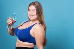 Recht überladene Dame, die Flasche Wasser hält Stockfoto