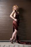 Recht überzeugtes blondes Mädchen im Abendkleid. Stockfotografie