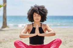 Recht afroe-amerikanisch Frau, die auf Strand meditiert Lizenzfreies Stockfoto