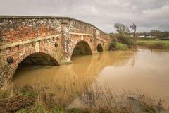 Recht alte Ziegelsteinbrücke über überschwemmtem Fluss stockfotografie