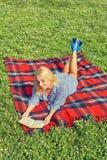 Recht anziehende blonde Frau, die auf einer roten Wolldecke im Freien liegt Stockbilder