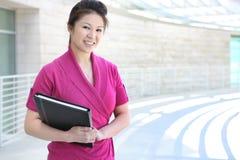 Recht asiatische Geschäftsfrau am Bürohaus Stockbild