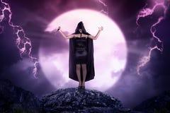 Recht asiatische Hexenfrau mit dem Mantel, der scharfes Messer hält Lizenzfreie Stockfotos