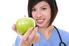 Recht asiatische Krankenschwester mit Apple Lizenzfreie Stockbilder