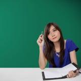 Recht asiatischer Student, der oben nach Inspiration, auf grünem Hintergrund sucht Stockbild