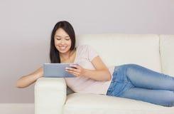 Recht asiatisches Mädchen, das auf dem Sofa unter Verwendung der digitalen Tablette liegt Stockfotos