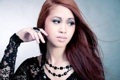 Recht asiatisches Mädchen mit dem langen Haar und Luxus schellt Stockfoto