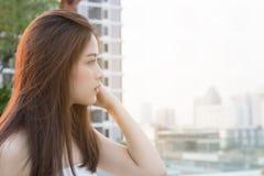 Recht asiatisches Mädchen, welches die Stadt betrachtet stockbild
