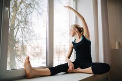Recht athletisches blondes Mädchen in der schwarzen Sportkleidung, die nahe dem Fenster heraus schaut sitzt Entspannung durch pil Stockbild