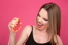 Recht begeisterte Frau, die Grapefruitsaft durch Hände zusammendrückt Lizenzfreies Stockfoto