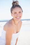 Recht blond auf dem Strand, der an der Kamera lächelt Stockfotografie