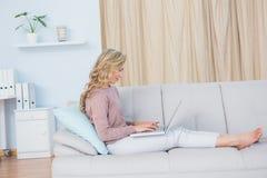 Recht blond auf der Couch, die auf Laptop schreibt Stockfotografie