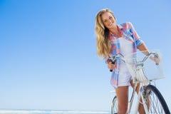 Recht blond auf einer Fahrradfahrt am Strand, der an der Kamera lächelt Lizenzfreie Stockfotos