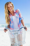 Recht blond auf einer Fahrradfahrt am Strand, der an der Kamera lächelt Stockfotografie