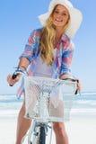 Recht blond auf einer Fahrradfahrt am Strand, der an der Kamera lächelt Lizenzfreie Stockbilder