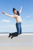 Recht blond in den Jeans, die auf den Strand springen Lizenzfreie Stockfotos
