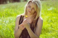 Recht blond in den sundress, die auf dem Gras hält gelbe Blume sitzen Lizenzfreies Stockbild