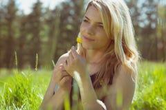 Recht blond in den sundress, die auf dem Gras hält gelbe Blume sitzen Lizenzfreies Stockfoto