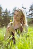 Recht blond in den sundress, die auf dem Gras hält gelbe Blume sitzen Stockfotos