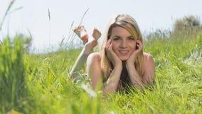 Recht blond in den sundress, die auf dem Gras lächelt an der Kamera liegen Stockbild