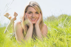 Recht blond in den sundress, die auf dem Gras lächelt an der Kamera liegen Stockfotos