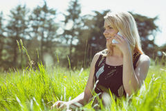 Recht blond in den sundress, die auf dem Gras spricht am Telefon sitzen Lizenzfreie Stockfotografie