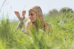 Recht blond in den sundress, die auf Gras liegen Stockfoto