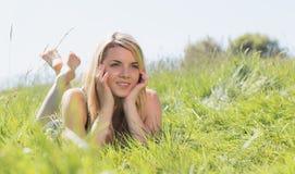 Recht blond in den sundress, die auf Gras liegen Stockbild