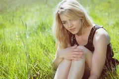 Recht blond in den sundress, die auf Gras sitzen Stockfotografie