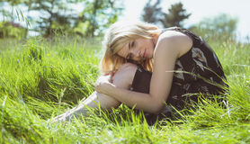 Recht blond in den sundress, die auf Gras sitzen Lizenzfreie Stockfotografie