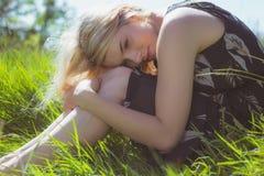 Recht blond in den sundress, die auf Gras sitzen Stockfoto