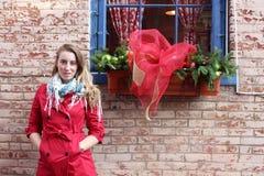 Recht blond in der roten Jacke gegen Backsteinmauer Stockbild