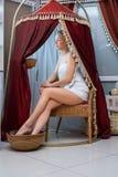 Recht blond im Badekurortsalon, der in einem Festzelt sitzt Lizenzfreies Stockbild