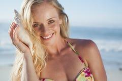 Recht blond im Bikini, der auf Tritonshorn auf dem Strand hört Stockfoto