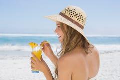 Recht blond im Bikini, der Cocktail auf dem Strand hält Stockfotos