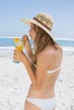 Recht blond im Bikini, der Cocktail auf dem Strand hält Lizenzfreie Stockfotografie