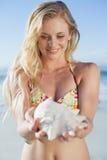 Recht blond im Bikini, der Tritonshorn auf dem Strand hält Lizenzfreies Stockfoto