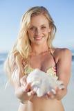 Recht blond im Bikini, der Tritonshorn auf dem Strand hält Stockfotografie