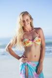 Recht blond im Bikini und in Sarongen, die an der Kamera auf dem Strand lächeln Lizenzfreies Stockbild