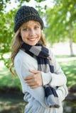 Recht blond im Hut und in Schal, die an der Kamera im Park lächeln Lizenzfreie Stockfotografie
