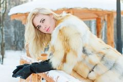 Recht blond im Pelzmantel, Lederhandschuhe wirft am Winter auf Stockfoto