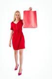 Recht blond im roten Kleid, das Einkaufstasche hält Lizenzfreie Stockfotografie