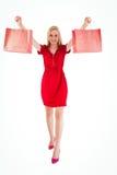 Recht blond im roten Kleid, das Einkaufstaschen hält Stockfoto