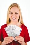 Recht blond im roten Kleid, das ihr Bargeld zeigt Stockfotos