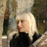 Recht blond im Schwarzen gegen Baumstamm. Lizenzfreie Stockfotos