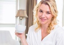 Recht blond im trinkenden Kaffee des Bademantels, der an der Kamera lächelt Stockfotos