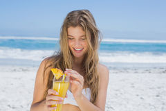 Recht blond im weißen Bikini, der Cocktail auf dem Strand hält Lizenzfreie Stockbilder